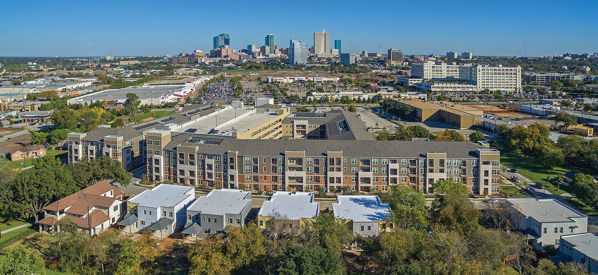 Aerial view of a large brown and white apartment complex with red brick and views of downtown Fort Worth