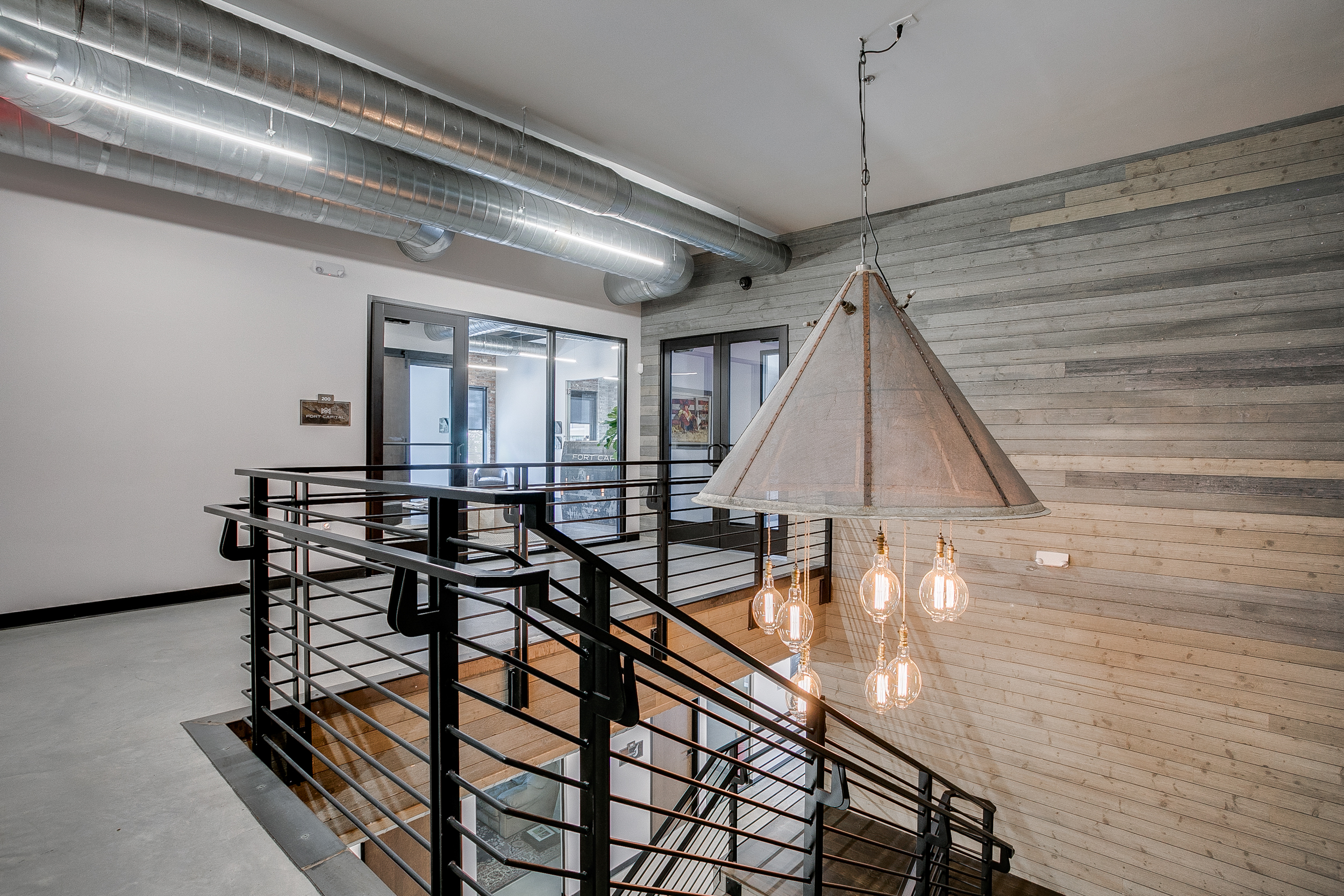 Top view of a black staircase, a wooden wall in the background, and a light fixture with dangling white light bulbs