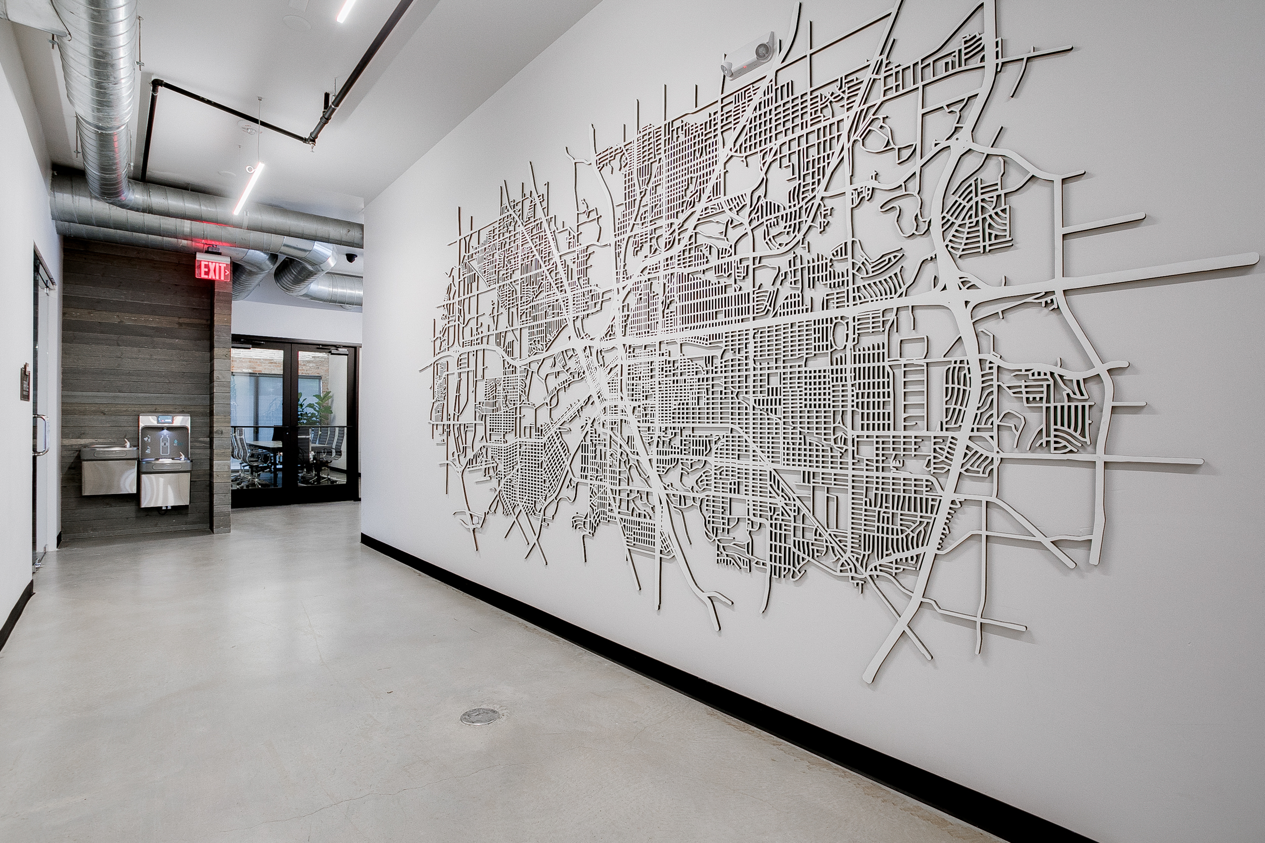 View of a white, three-dimensional map of Fort Worth on a blank white wall and a wooden wall with a water fountain