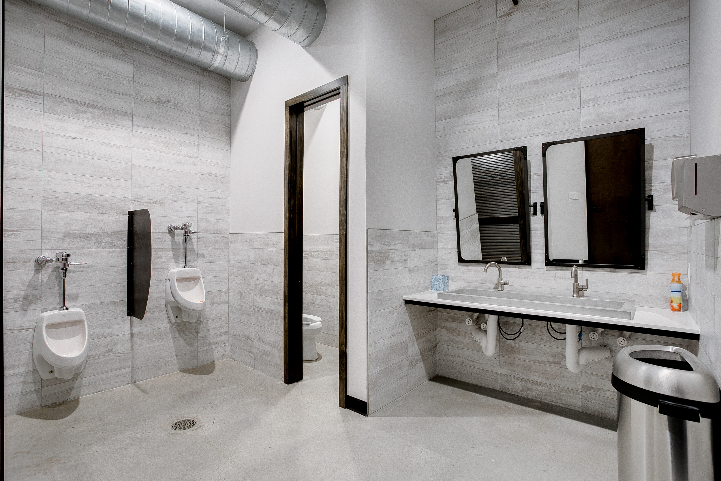 View of the men's restroom inside of 105 Nursery Lane with grey tiled floors and walls, a sink, wooden mirrors, and urinals