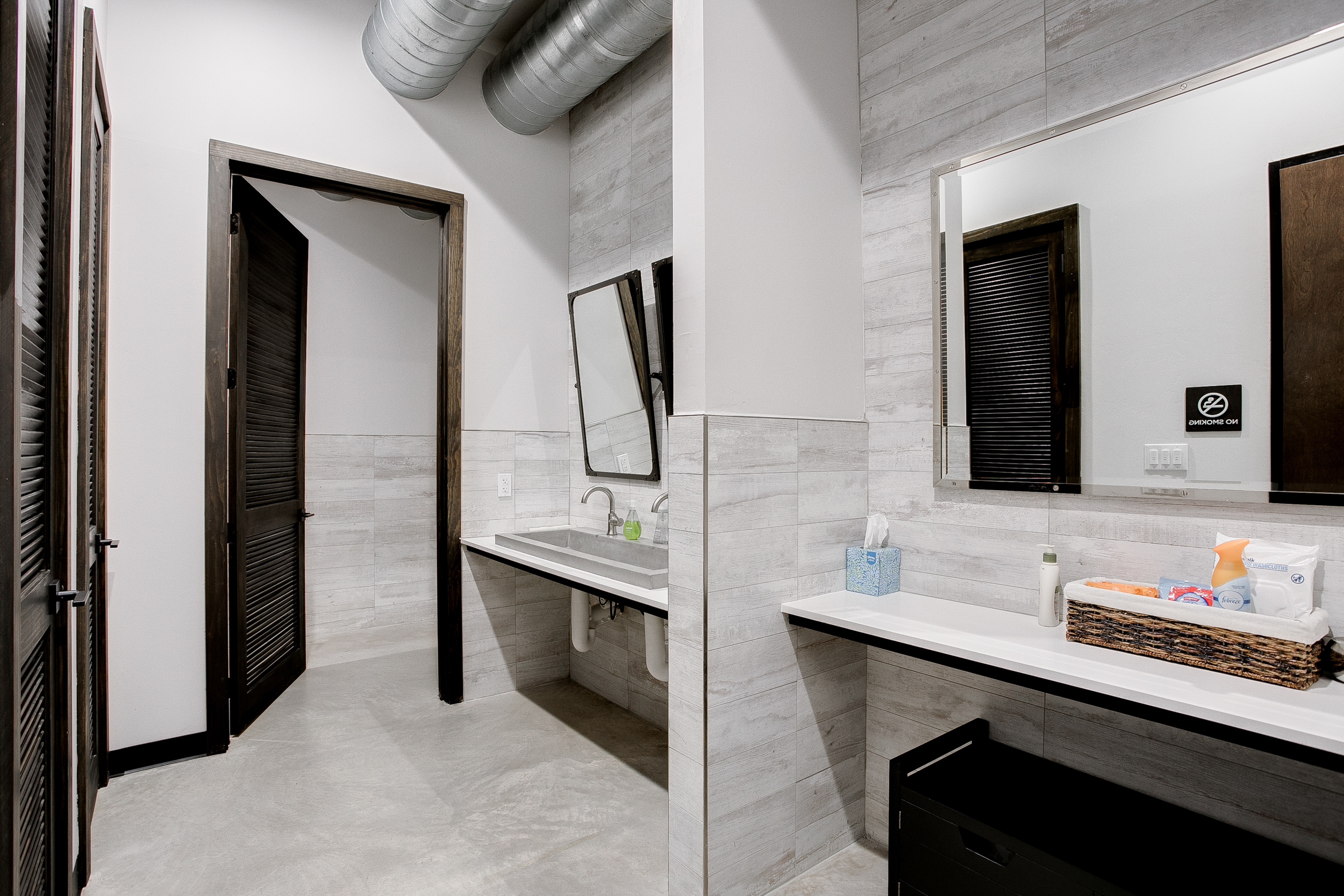 View of the women's restroom inside of 105 Nursery Lane with grey tiled floors and walls, and wooden doors for each stall