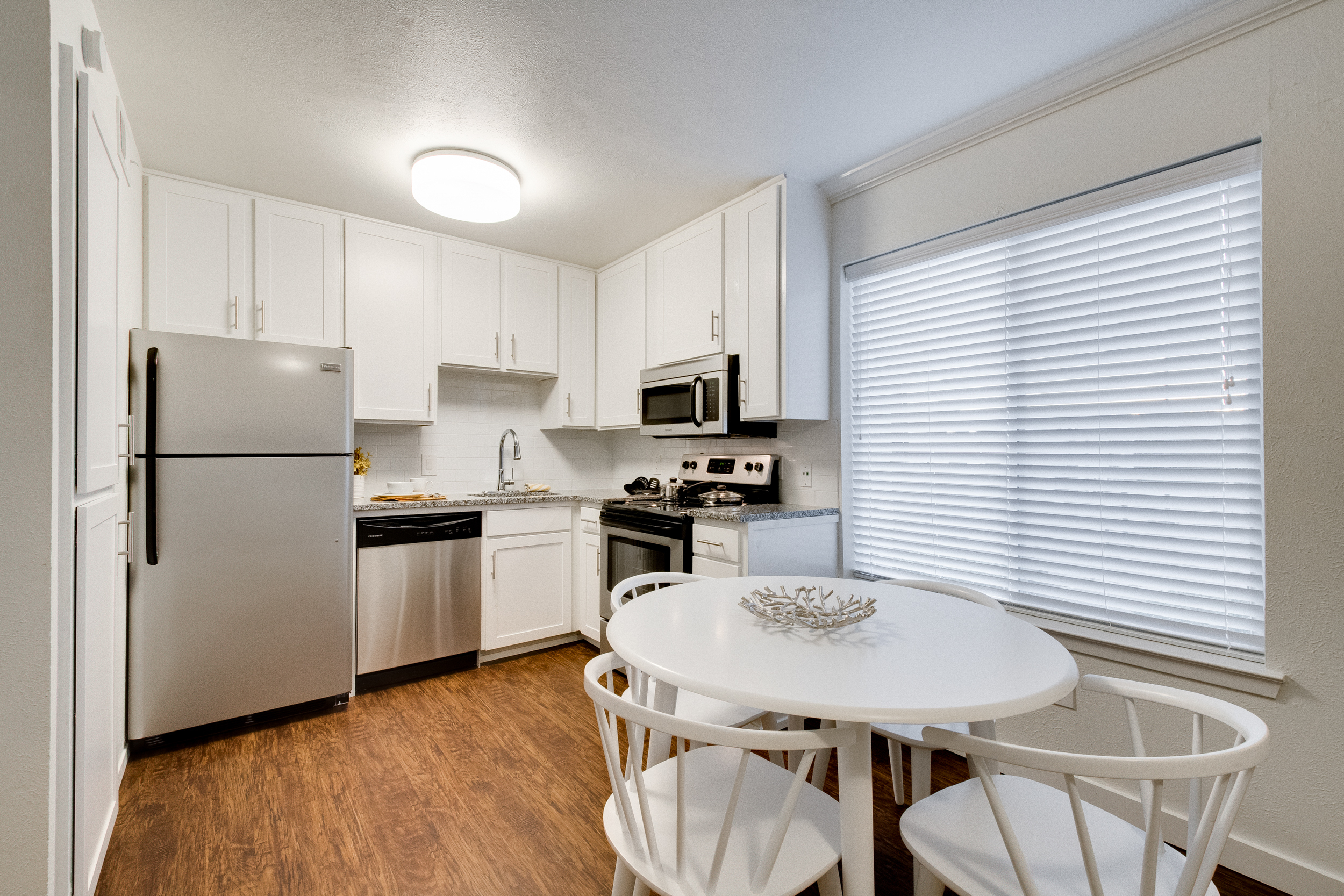 Interior view a kitchen area with white cabinets, stainless steel appliances, and and a white table with four chairs