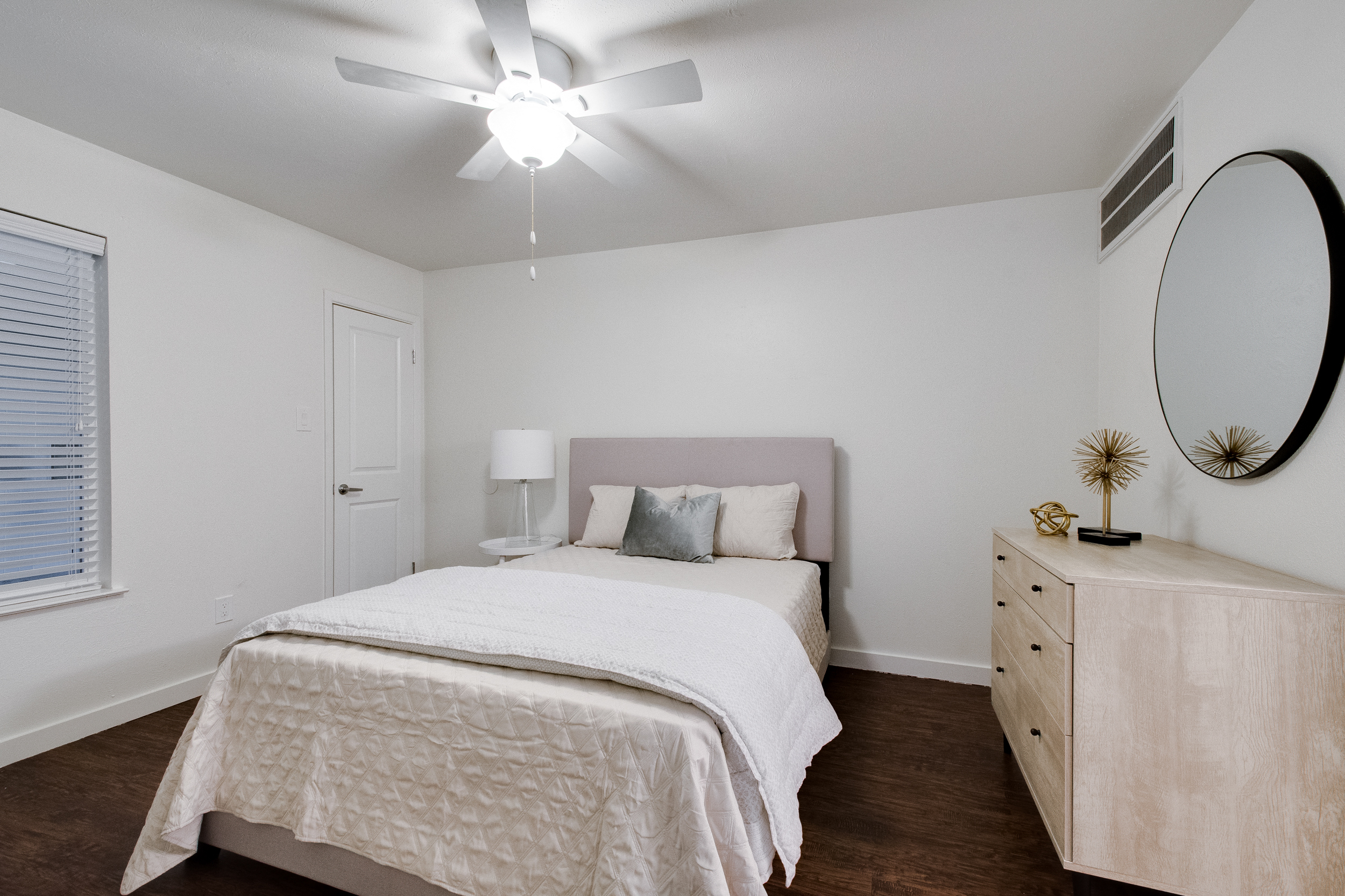 Interior view of a bedroom with white sheets, a wooden dresser, gold accent decorations, and a circular mirror