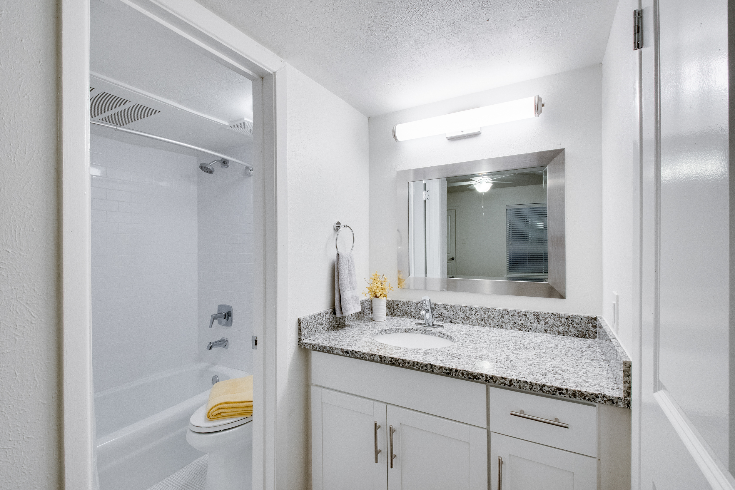 Interior view of a bathroom with white cabinets, grey granite countertops, and a door leading to a toilet and shower