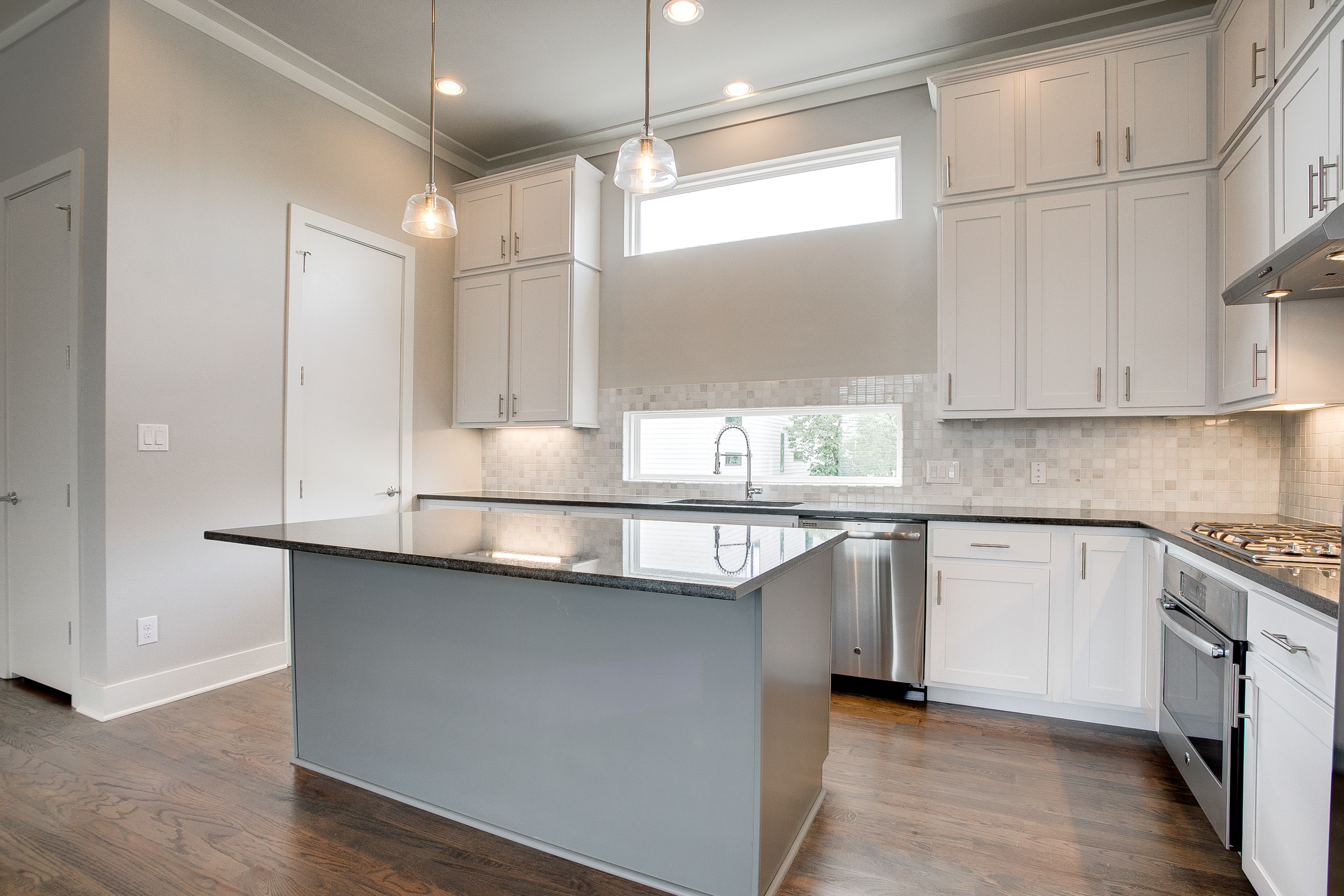 Interior view of a kitchen with white cabinets, white tile backsplash, stainless steel appliances, and a center island