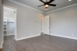 Interior view of an empty bedroom with dark hardwood floors, a ceiling fan, and a view into the walk-in closet