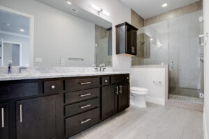 Interior view of the bathroom with dark cabinets, double sinks, a toilet, and a tiled shower with a glass door