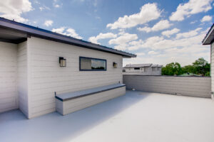 Exterior view of the rooftop deck of the townhome with white siding, a black roof, and views of the surrounding area