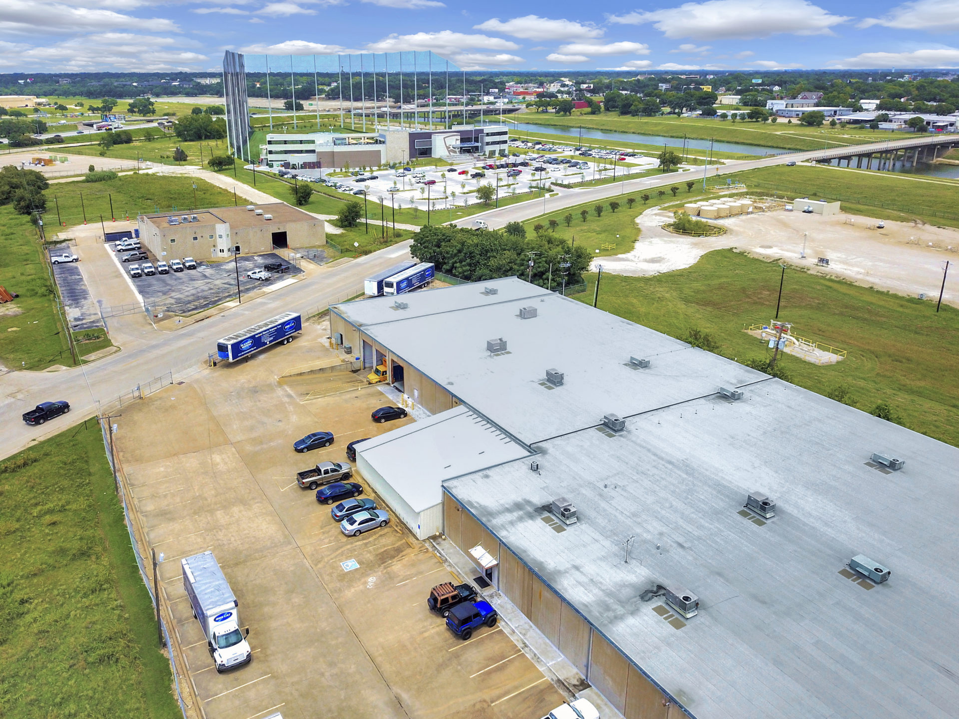 Aerial view of a tan building with a grey roof and a lot of trailers and cars with views of Top Golf in the background
