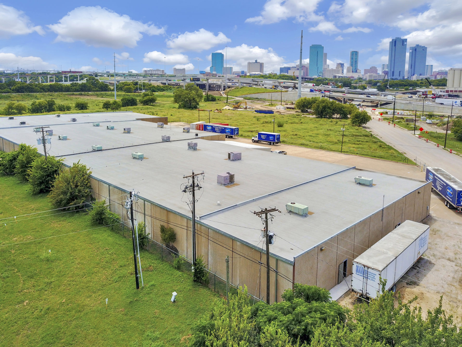 Aerial view of the backside of a tan building with a grey roof with power lines and a view of downtown Fort Worth