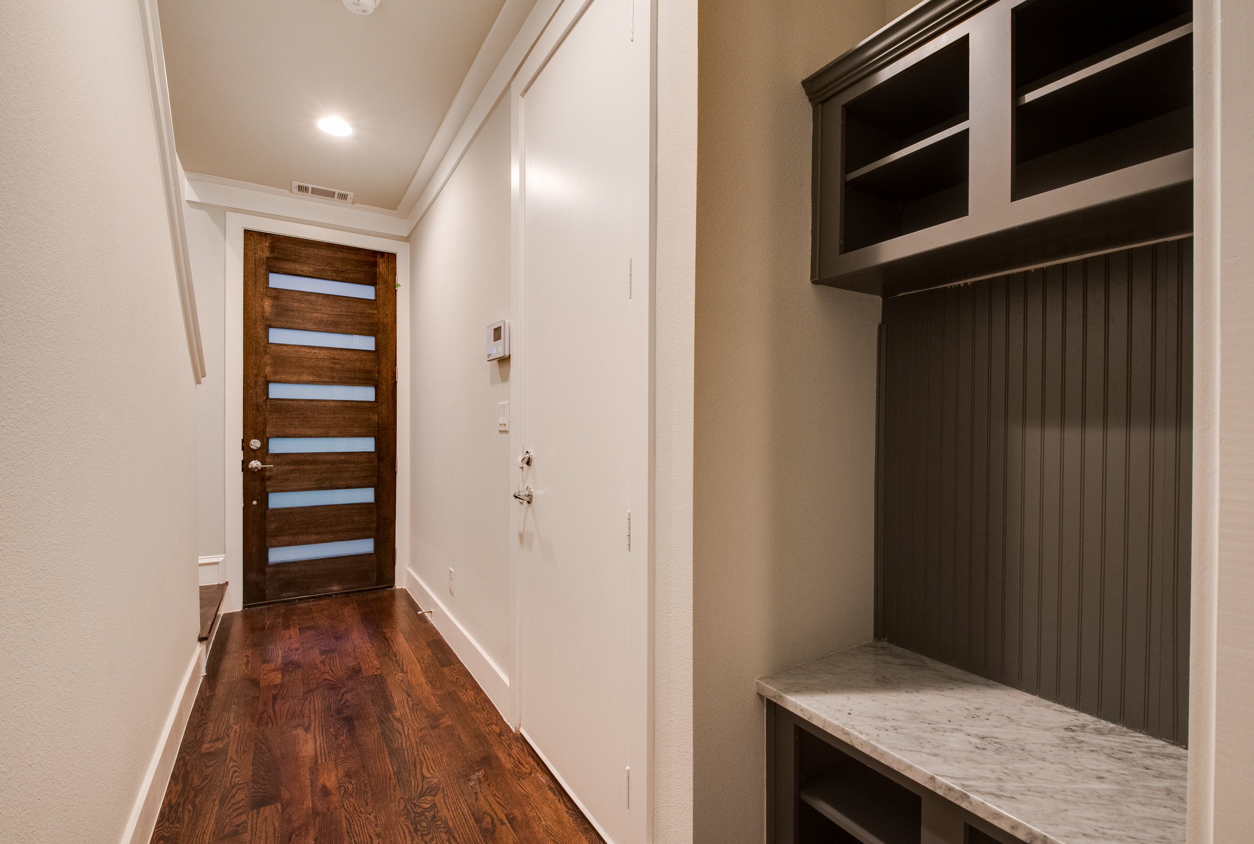 Interior view of the front entry hallway with dark wooden floors and a black shelving unit with a bench seat