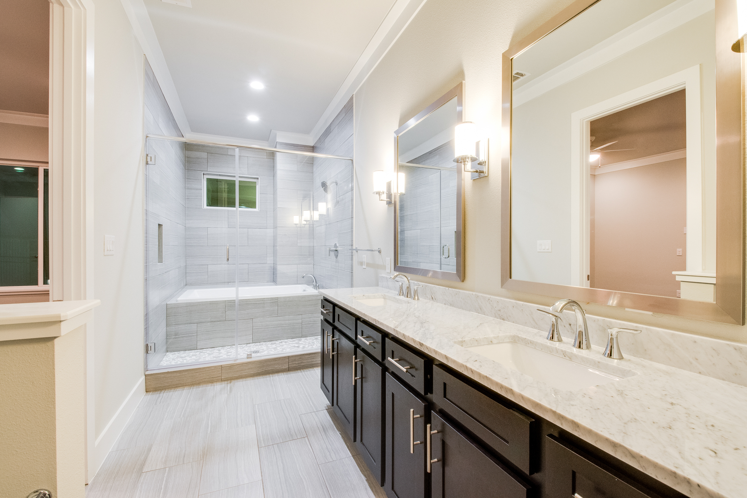 Interior view of the bathroom with two sinks, dark cabinets, light granite countertops, and a grey tiled shower with a bench