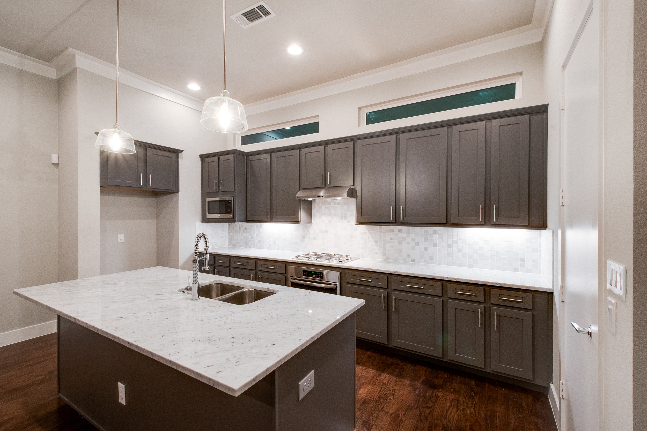 Interior view of the kitchen with dark cabinets, stainless steel appliances, and a large center island with light countertops