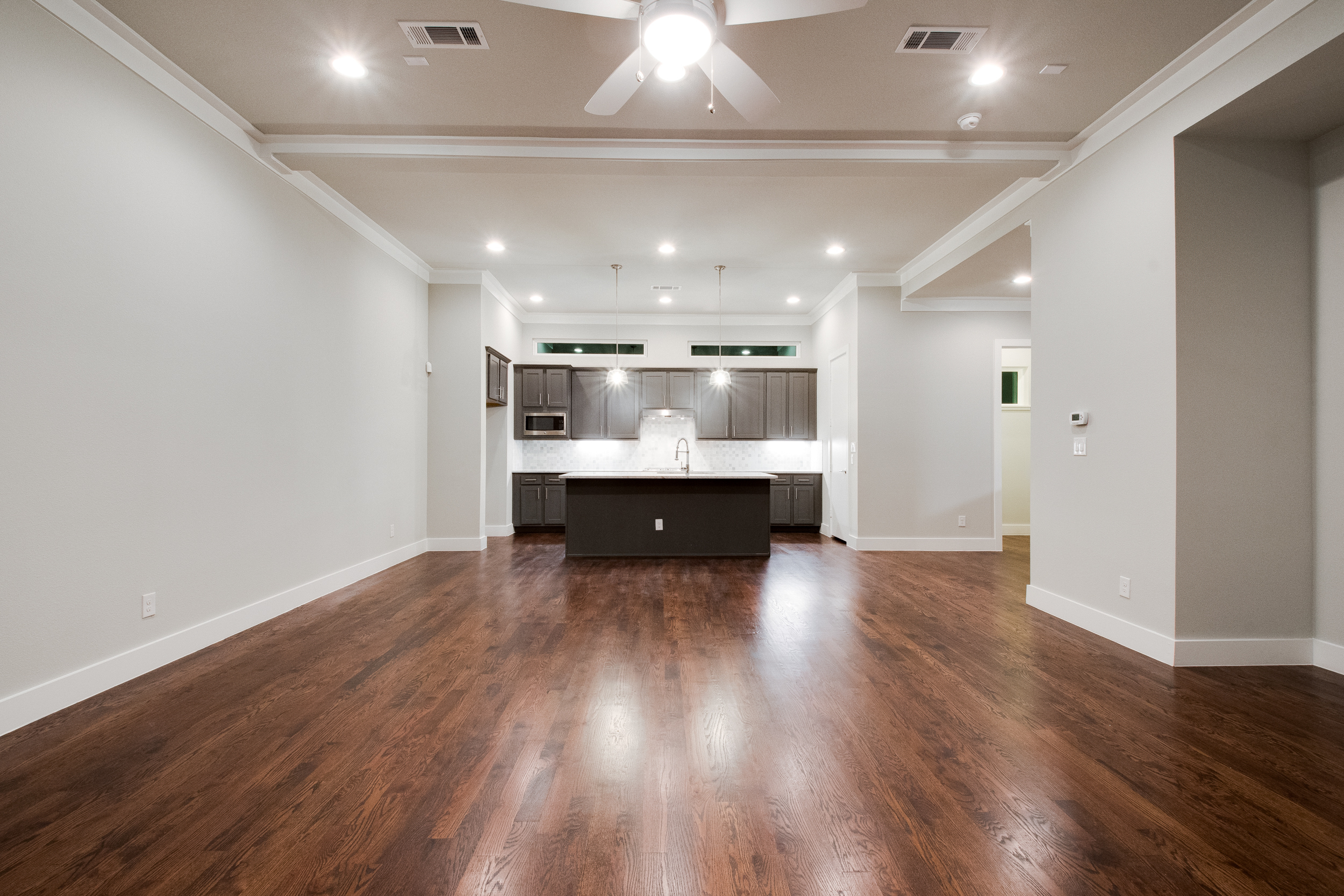 Interior view of the empty living room with dark wood floors, white crown molding and a view into the kitchen