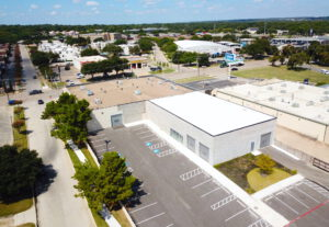 Aerial view of the backside of a light grey building with a white and brown roof and various different parking spaces