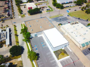 Aerial view of an L-shaped building with a white and brown roof with parking spaces next to the adjacent street
