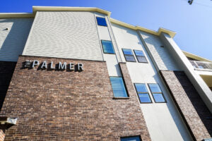 """Exterior, close-up view of the red and brown brick with grey lettering that says """"The Palmer"""" on the side of the building"""
