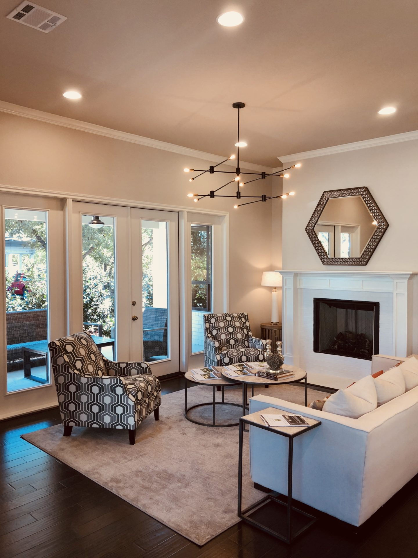 Interior view of a living room with a white fireplace, blue patterened chairs, and a clear door to the outside patio