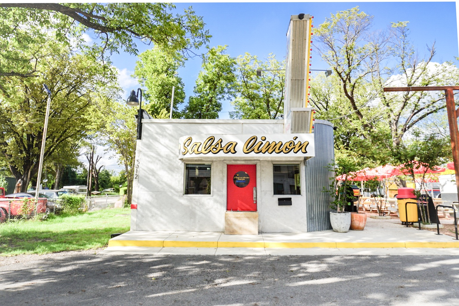 """Exterior, front view of a white building with a red front door and a yellow sign saying """"Salsa Limon"""" above the door"""