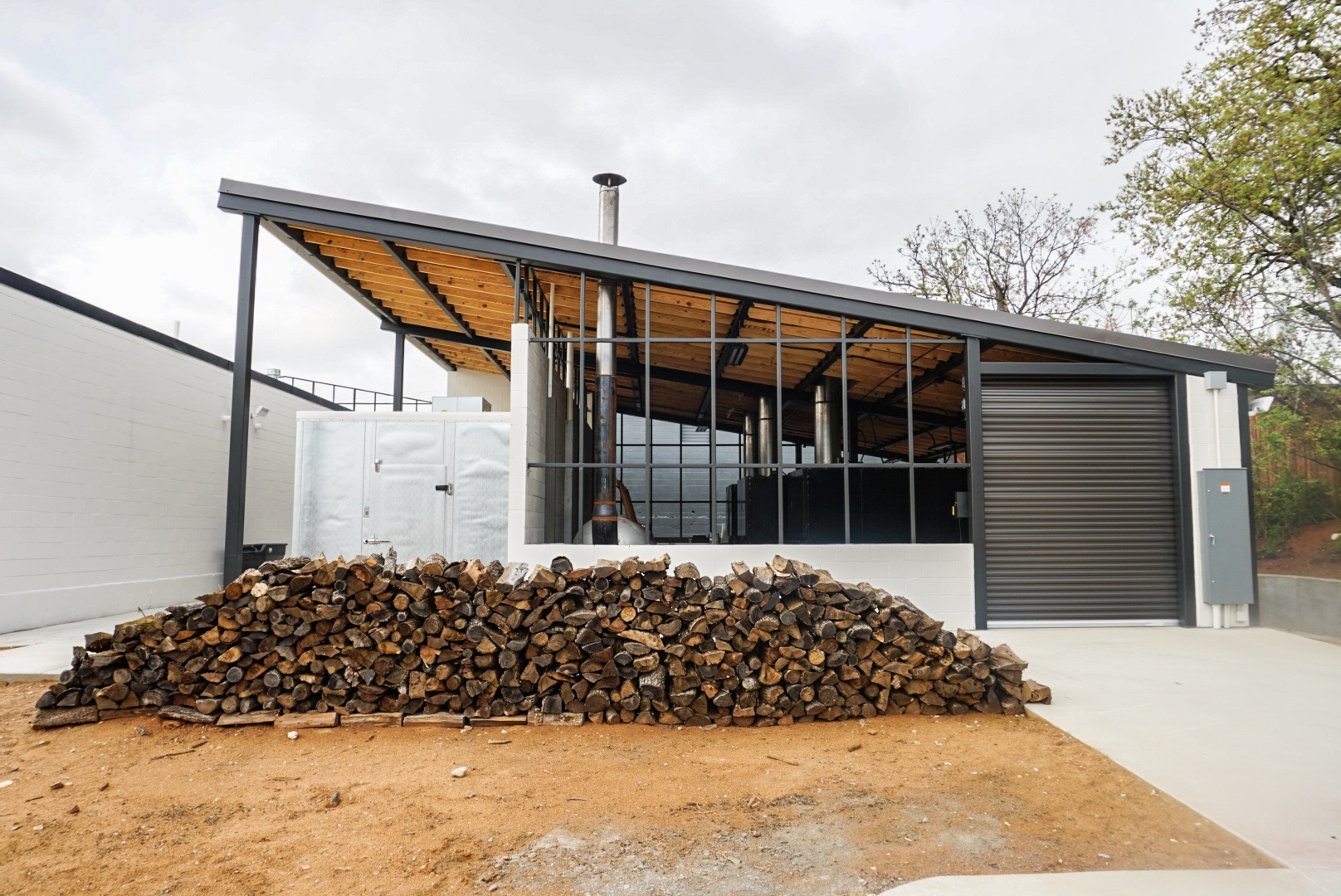 An exterior view of the backside of a white building with a garage door, a smoker, and a large pile of firewood