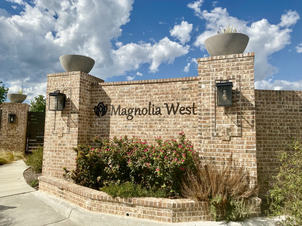 "Up-close exterior view of a red brick fence with two black light boxes and black lettering saying ""Magnolia West"""