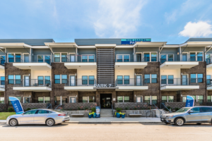 Exterior front view of the Park 7 Apartment complex with two cars parked in front of the building and various white balconies