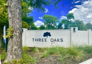 """Up-close view of black lettering saying """"Three Oaks"""" on a white brick fence with a trunk of a brown tree on the left"""