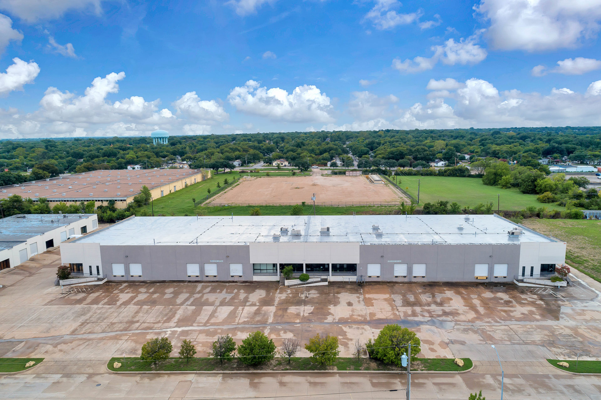 Aerial view of one building in the Suffolk Business Park with grey and white siding, entrance ramps, and loading docks