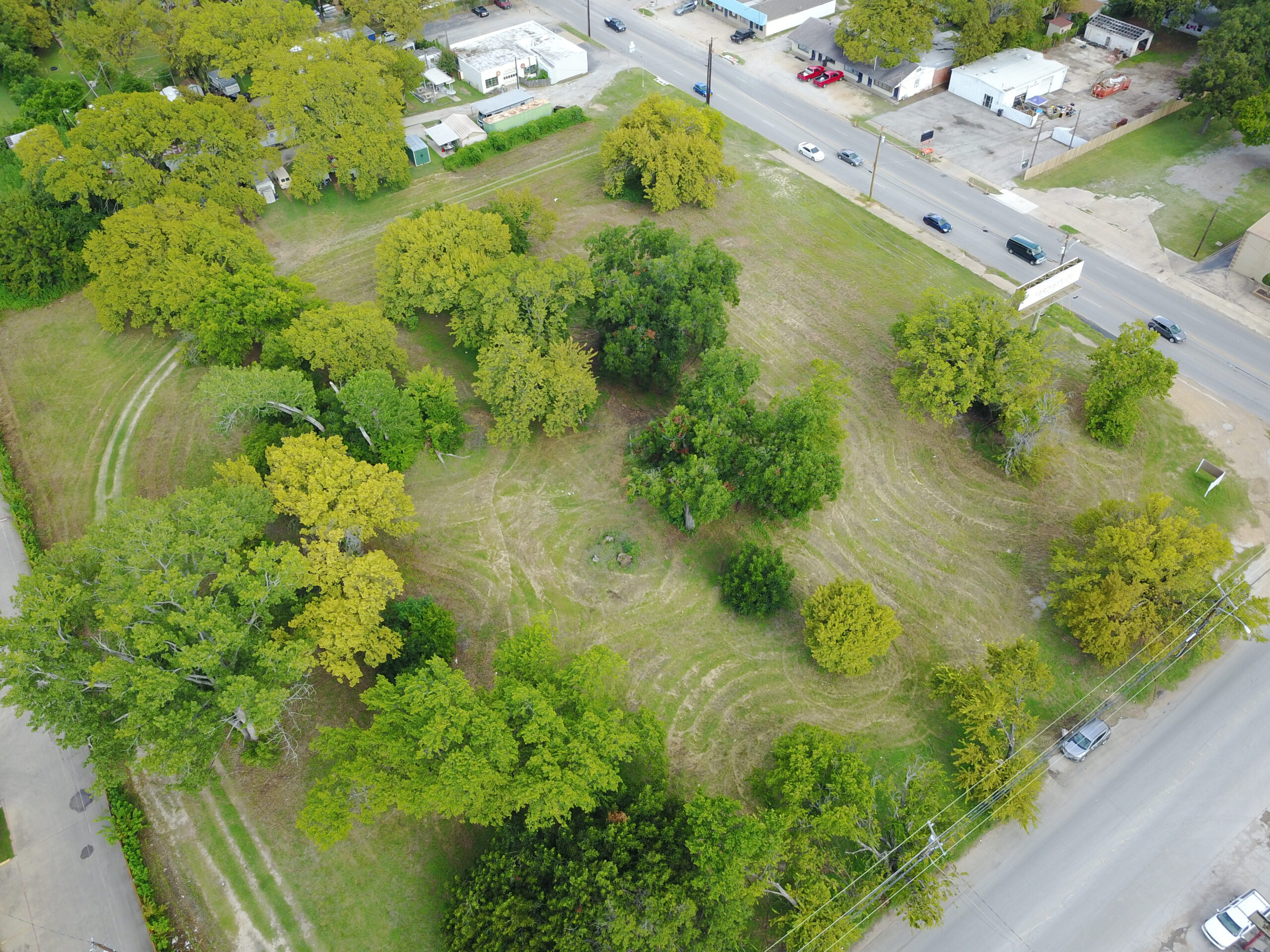 Birds-eye view of a grassy, square plot of land with numerous light and dark green trees throughout the land