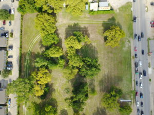 Birds-eye view of a grassy plot of land with trees adjacent to a parking lot on one side and a street on the other