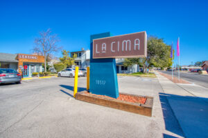 "Exterior view of a blue vertical post with a horizontal sign with white lettering saying ""La Cima"" in a parking lot"