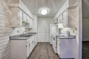 Interior view of a galley style kitchen with white cabinets, white appliances, grey wooden floors, and grey countertops