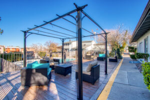 Exterior view of a black pergola with black wicker chairs, tan and blue cushions, on a wooden patio next to a pool