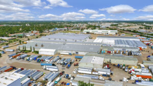 Aerial view of 4040 Forest Lane showing multiple tin-roofed warehouse buildings with numerous trailers parked outside