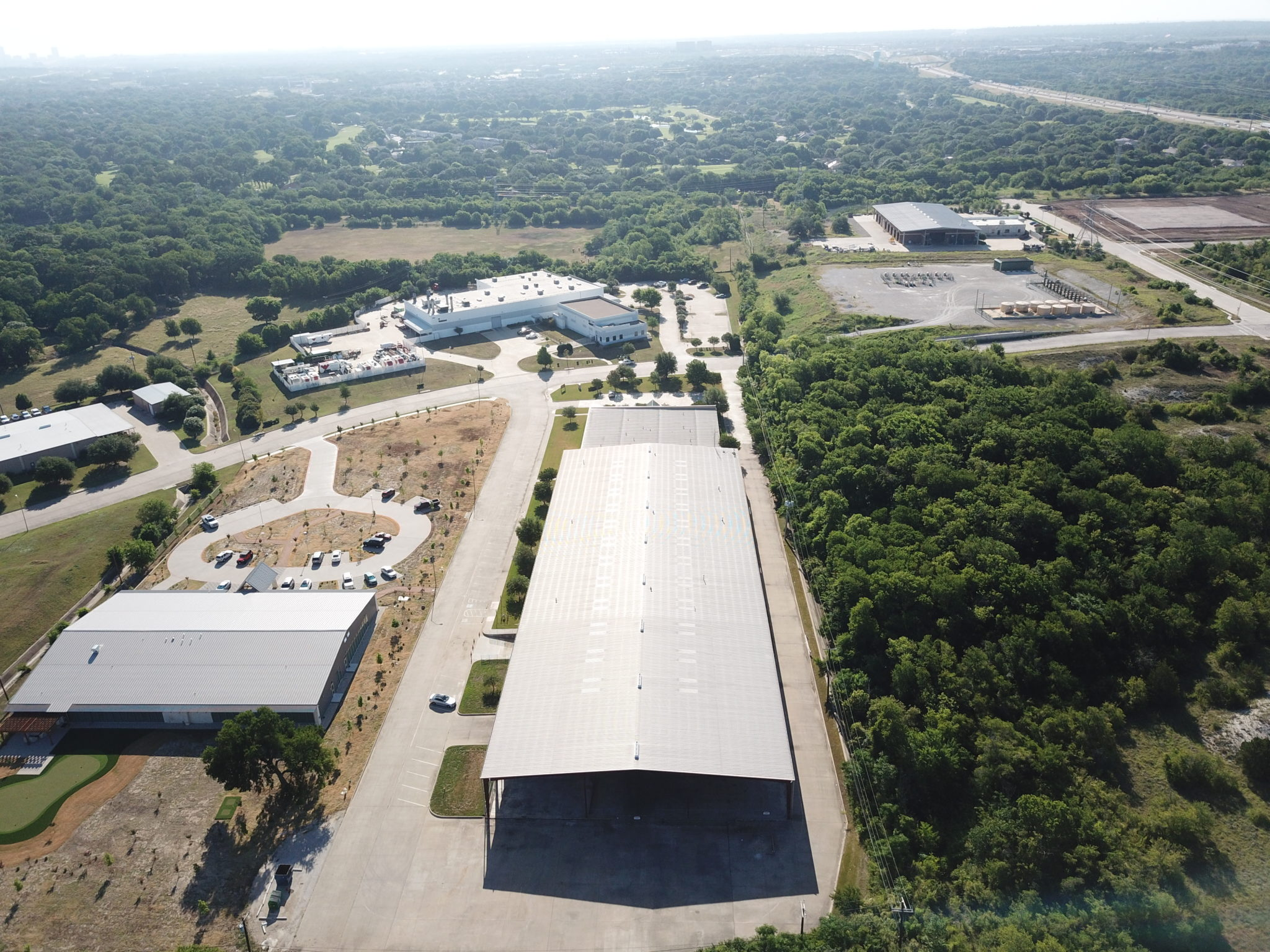 Aerial view of the silver roof of 7471 Benbrook Parkway showing the surrounding buildings and greenery in the background