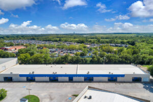 Aerial view of a white building with blue siding, multiple blue loading docks and a full lot of cars in the background