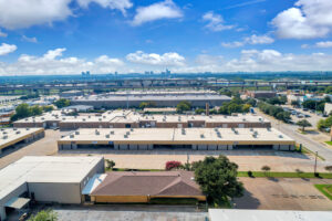 Aerial view of multiple large, warehouse buildings with parking spaces in front and views of the city in the background