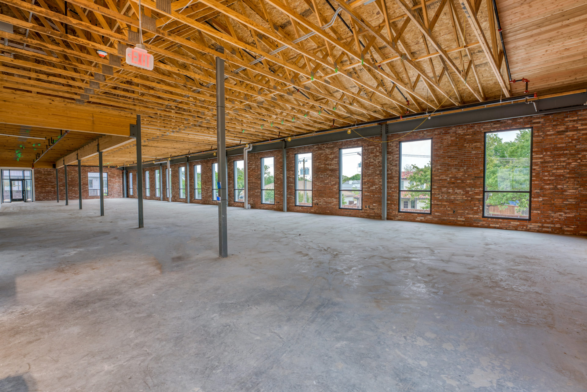 Interior view of the ground floor of 133 Nursery Lane with unfinished ceilings and a brick wall on the right side