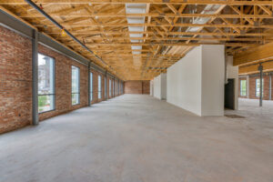 Interior view of second floor of 133 Nursery Lane with a brick wall on the right side and steel beams throughout