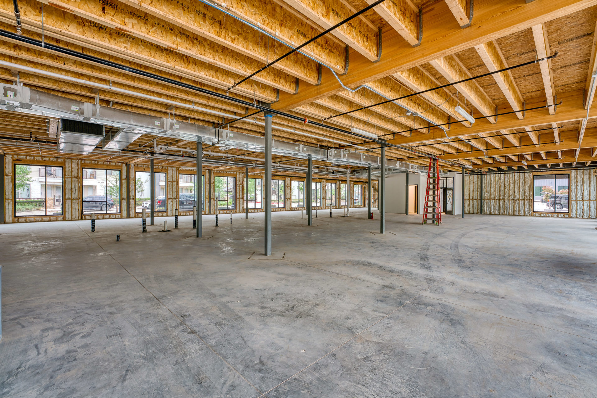 Interior view of 133 Nursery Lane with unfinished ceilings, cement flooring, and grey steel beams throughout the space