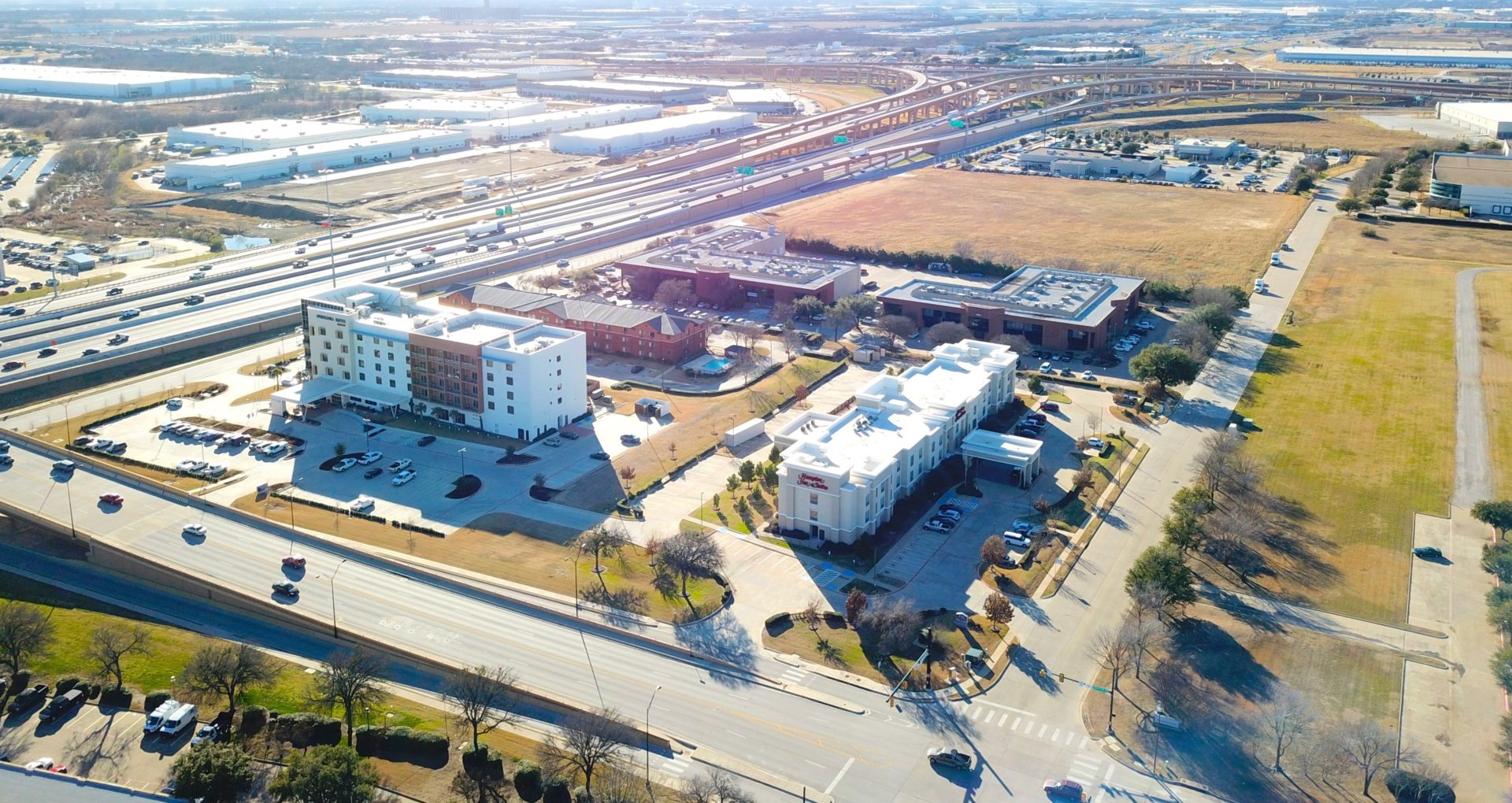 Aerial view of the two Fossil Creek Place buildings with the surrounding parking lots and hotels and adjacent highways