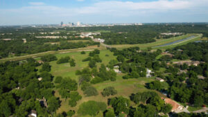 Zoomed out aerial view of a large farm with numerous trees and a view of the Trinity River and downtown Fort Worth
