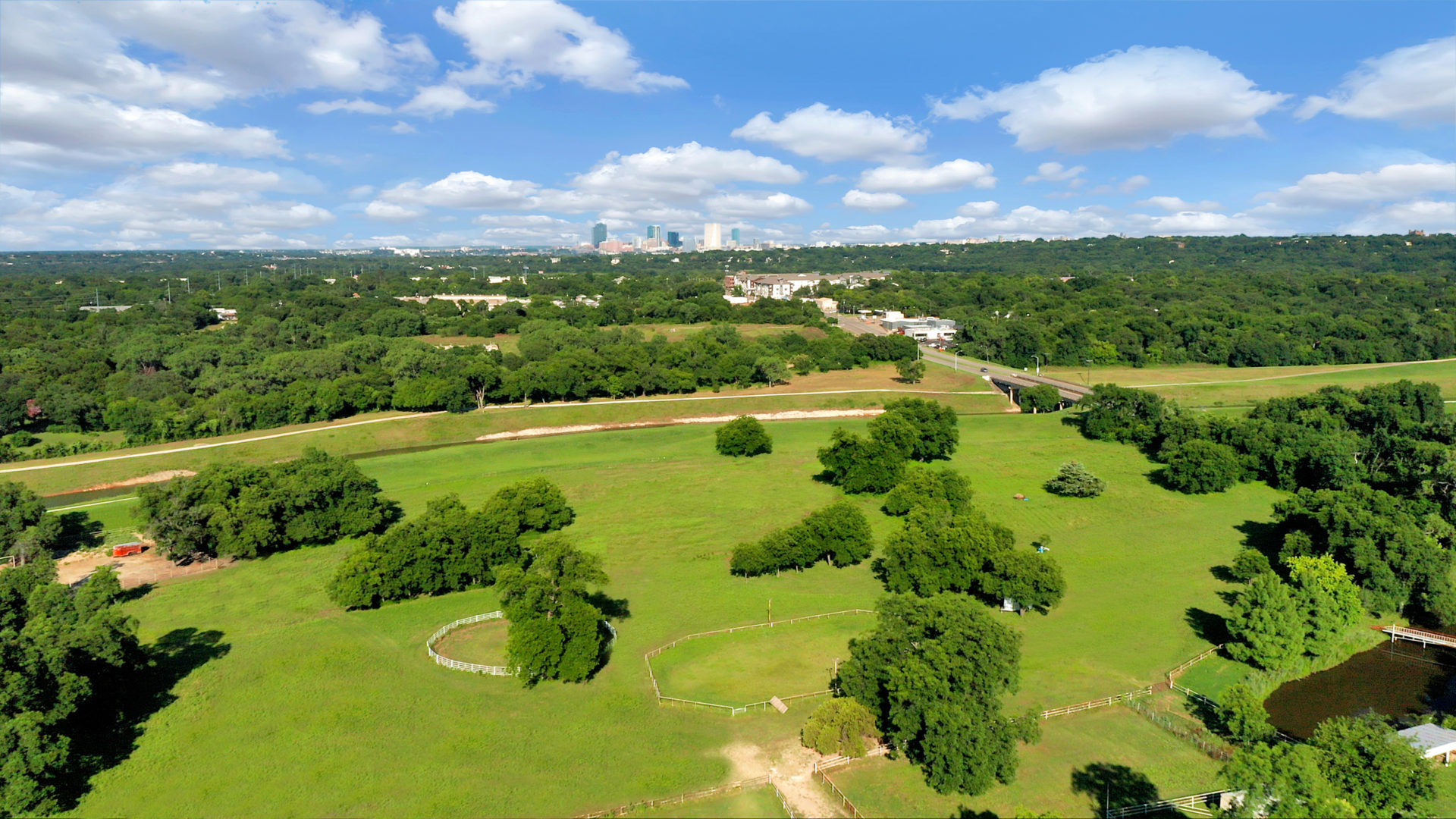 Aerial view of a green farm with multiple trees adjacent to a river and road with a view of downtown Fort Worth