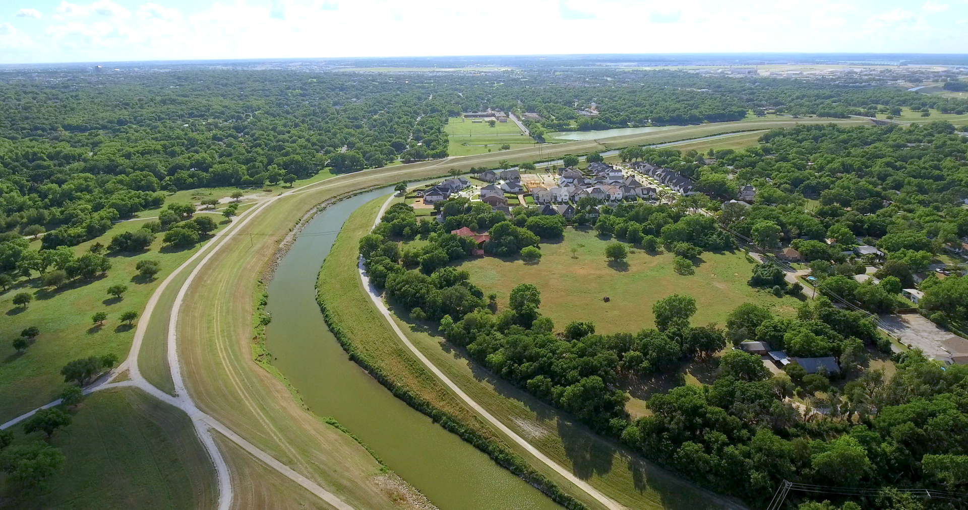 Aerial view of the horseshoe bend of the Trinity River surrounded by numerous green trees and houses in the background