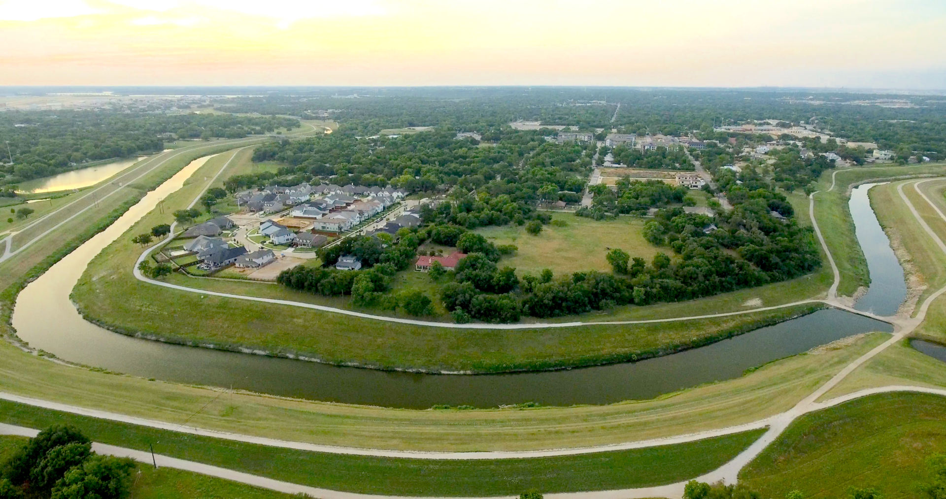 Aerial view of the horseshoe bend of the Trinity River with numerous green trees and developments in the background