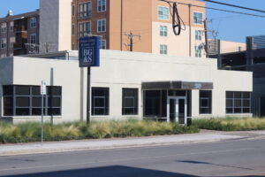 Ground-level view from the adjacent street of a grey building with black windows, a brown wooden onning, and a tall blue sign