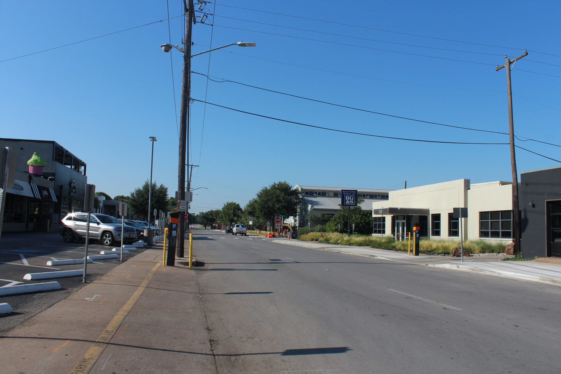 Ground-level view of a street with a stop sign, a grey building on the right, a parking lot on the left, and an electric line