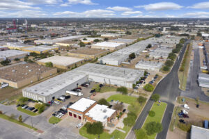 Aerial view of the Arlington Industrial Portfolio with one white, L-shaped building with many trucks and cars parked in front