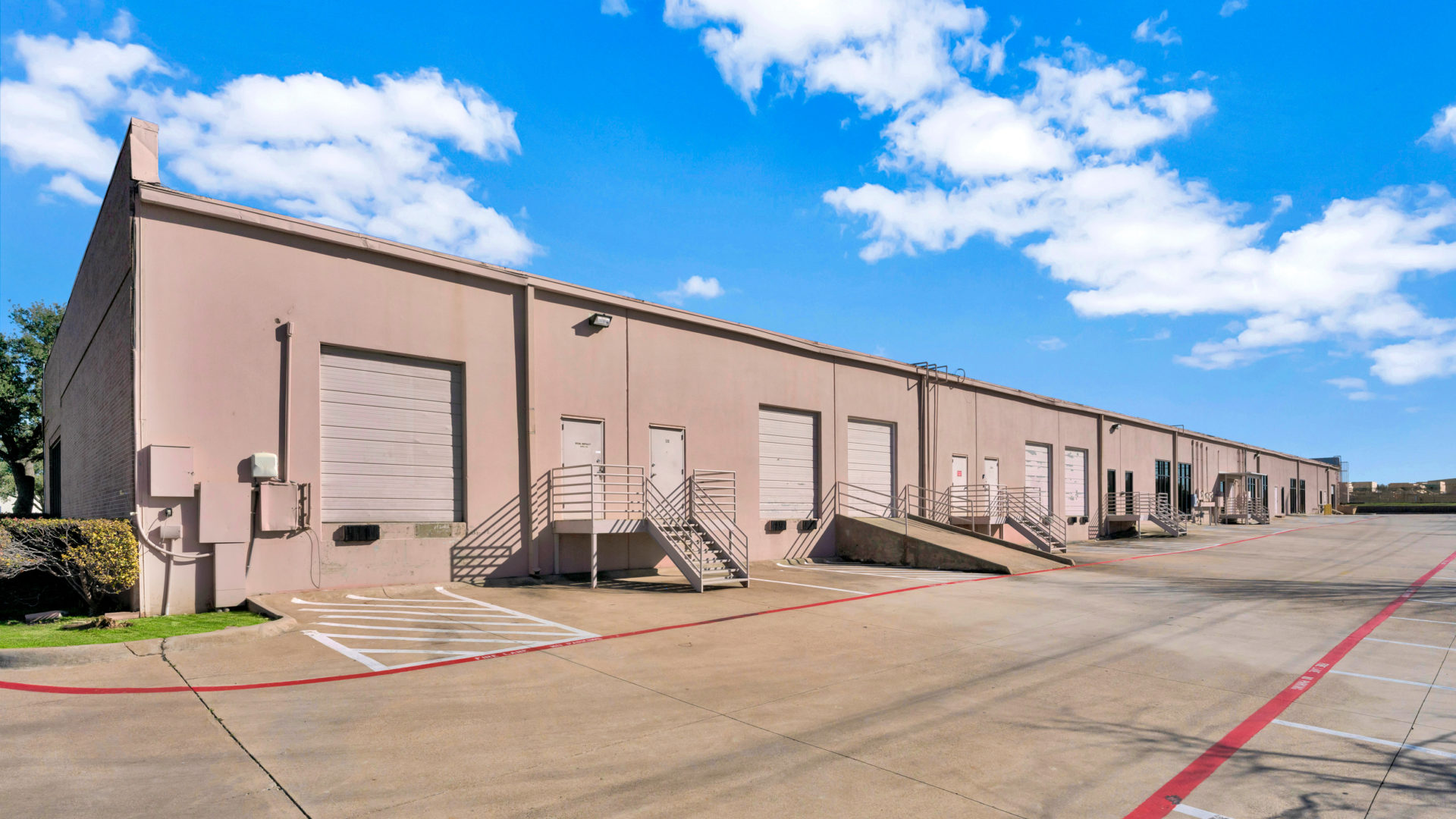 Up-close view of the backside of the Avion Business Park with multiple garage doors, loading docks, and truck ramps