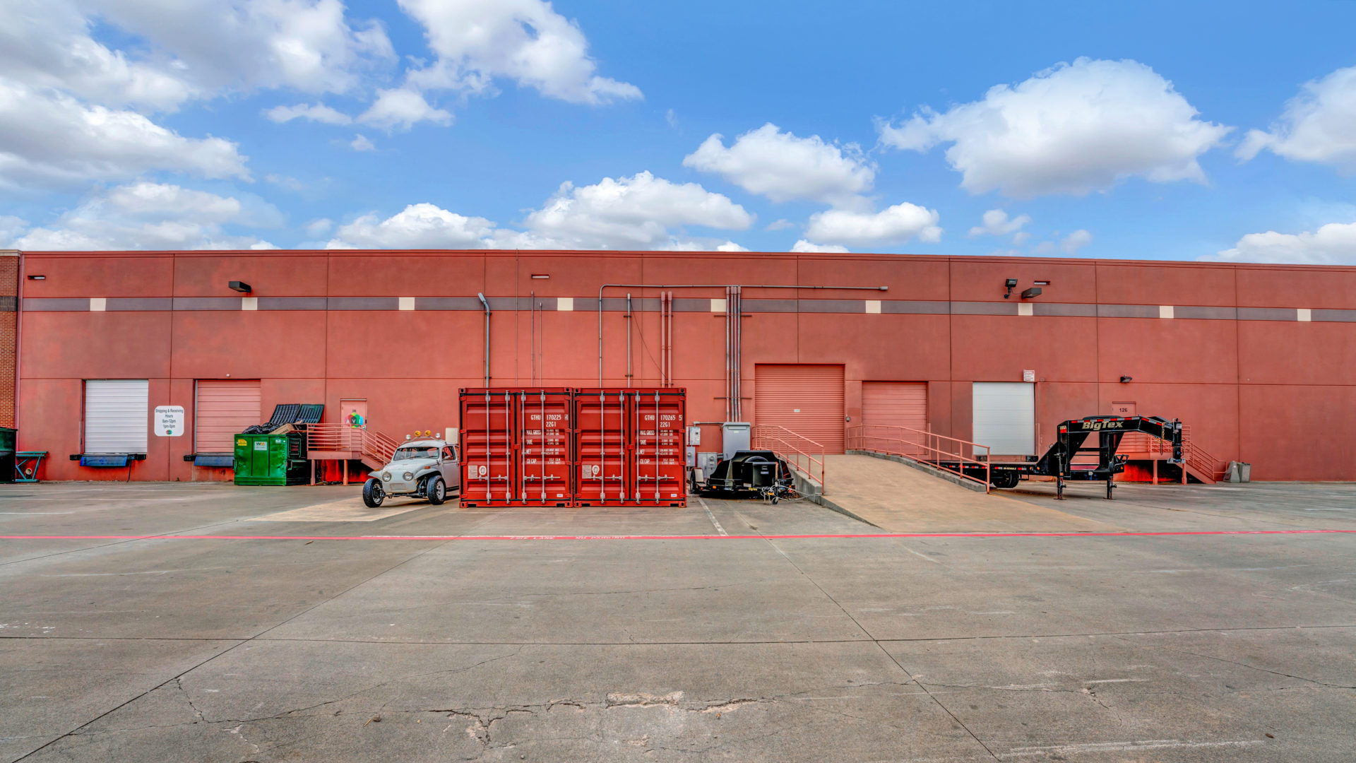 Up-close view of the backside of 4040 Royal Lane showing multiple shipping containers and loading docks